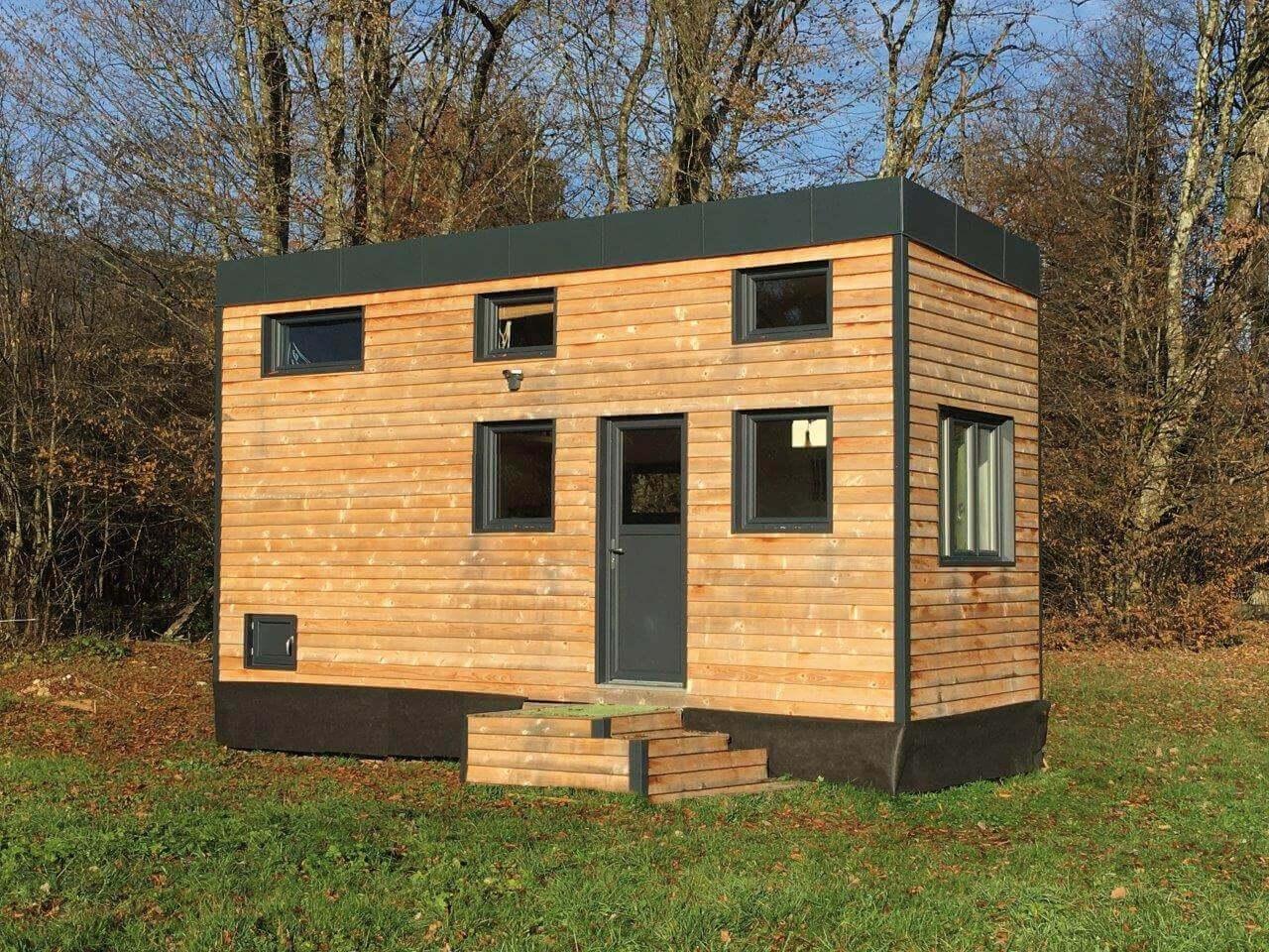 Tiny house en bois vue de l'extérieur dans un champ