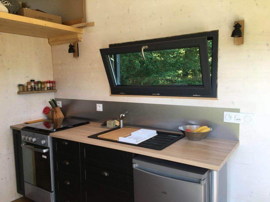cuisine de tiny house avec plan de travail et fenêtre ouverte